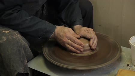 potter wheel : The elderly male hands of a potter make a vase from clay. An experienced potter creates a beautiful clay vase.