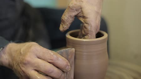 kamenina : An experienced potter creates a beautiful clay vase. The elderly male hands of a potter make a vase from clay.