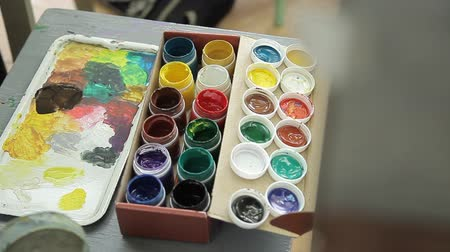 kutuları : .Open cans of gouache for drawing. Multi-colored paints of the artist. The artist draws yellow paint on a brush with a polytr. Stok Video