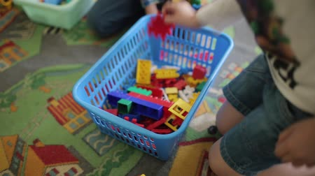 ladrillo : Children play with colored plastic toys. The game of cars. Two boys collect color plastic constructor. Little child playing with lots of colorful plastic toys indoor.