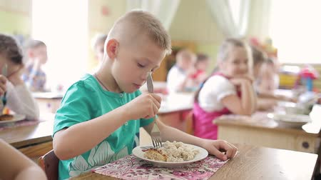 przedszkolak : The boy eats a cutlet with a fork in a preschool. Feeding children in kindergarten Wideo