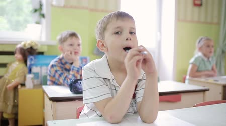 distraído : A boy holds a pencil in his mouth, thinking with a pencil in his mouth. A young boy holds a pencil in his mouth and solves the task.