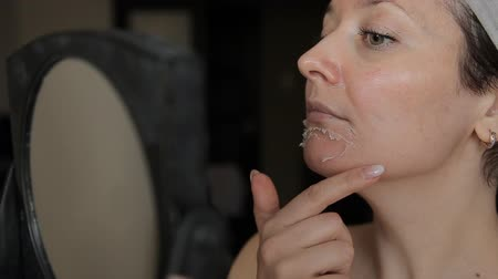 arcszín : A woman examines the peeling of her face in a mirror. Exfoliate old skin after peeling.