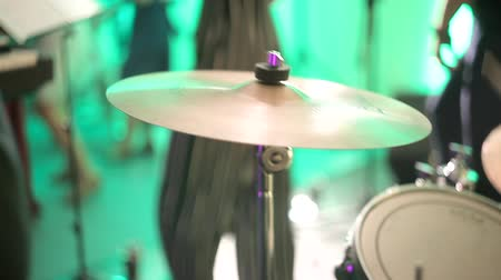 dourado : The drummer plays the drums, strikes the musical plates at the concert with his chopsticks. Concert performance on stage. Color light illuminates the cymbals of the drum set in close-up.