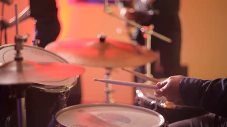 percussão : The drummer plays the drums, strikes the musical plates at the concert with his chopsticks. Concert performance on stage. Color light illuminates the cymbals of the drum set in close-up.