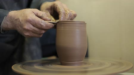 moldagem : An experienced potter creates a beautiful clay vase. The elderly male hands of a potter make a vase from clay.
