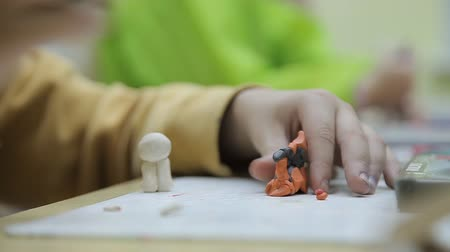 пластилин : Child sculpts a sculpture made of colored clay. The boy sculpts from colored plasticine. Стоковые видеозаписи