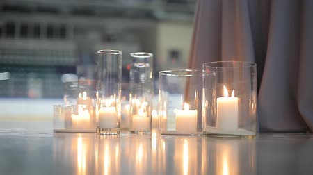 díszített : Burning white candles in a glass bulb stand on the ice of the stadium s rink. Large candles burn in glass flasks.