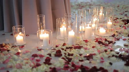 hazugság : White burning candles in glass flasks, rose petals lie on the ice. Romantic candlelight evening for lovers Stock mozgókép
