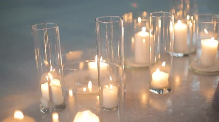 cera : Burning white candles in a glass bulb stand on the ice of the stadium s rink. Large candles burn in glass flasks.