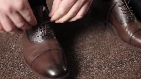 cadarço : Businessman man ties shoelaces on brown boots in a room. A man wears shoes. Tie your shoe laces. Mens style. To prepare for work, for a meeting. Vídeos