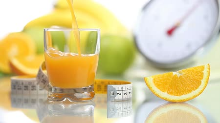 диета : orange juice poured in glass, fruit meter scales diet food Стоковые видеозаписи