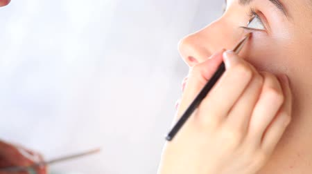 hand made : make-up artist die oogschaduw op ooglid met behulp van make-up borstel Stockvideo