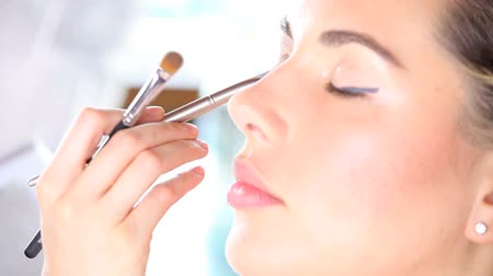 косметика : makeup artist applying eyeshadow on eyelid using makeup brush