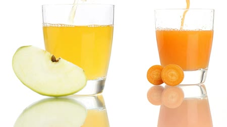 meyve suyu : apple and carrot juice poured in to the glass isolated on white background Stok Video