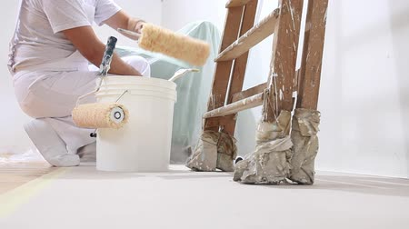 rolete : painter man at work, rests the paint roller in the bucket