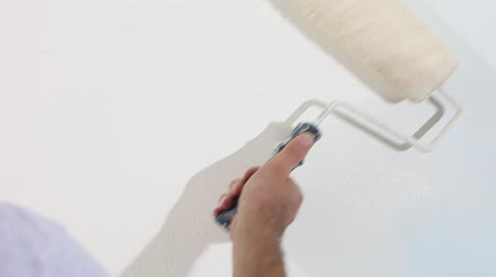 rolete : painter man at work, with roller painting wall, painter house concept Vídeos