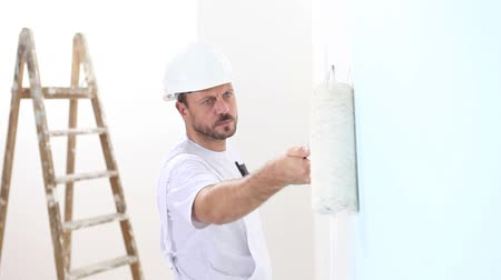 decorador : painter man at work, with roller painting wall, and wooden ladder in close up