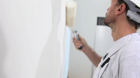 malarstwo : painter man at work, with roller painting wall, painter house concept Wideo