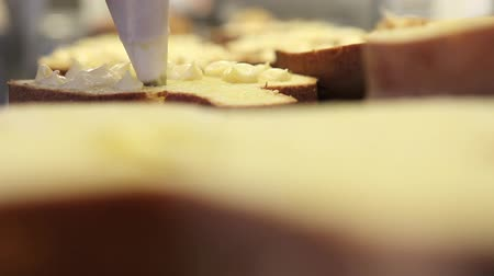pastry chef  hands stuffed Easter sweet bread cakes with custard, closeup on the worktop in confectionery Stock Footage