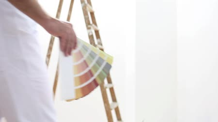 painter man at work with color swatches samples, wall painting concept, ladder in the background.