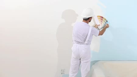 decorador : painter man at work with color swatches samples, wall painting concept, white copy space background. Stock Footage