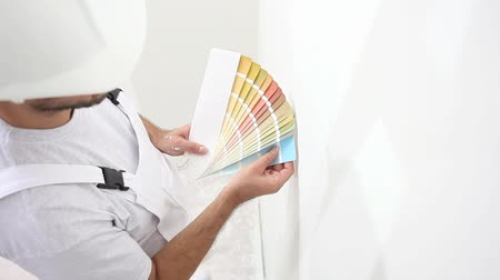 painter man at work with color swatches samples, wall painting concept, white copy space background. Stock Footage