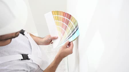 painter man at work with color swatches samples, wall painting concept, white copy space background. Dostupné videozáznamy