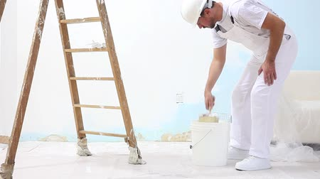painter man at work with brush, wall painting concept, white copy space background. Stock mozgókép