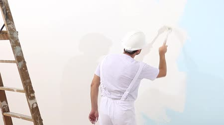 painter man at work with brush, wall painting concept, white copy space background. Dostupné videozáznamy
