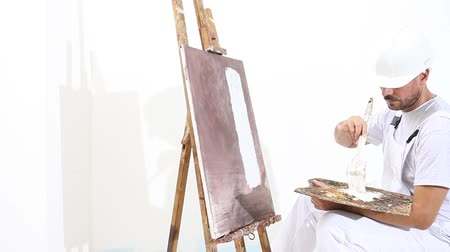 painter man at work with paint brush, easel, canvas and palette, wall painting concept, white copy space background. Stock Footage