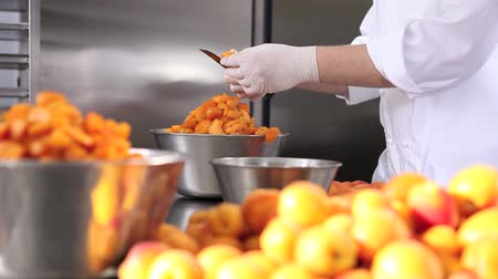 konzervált : hands pastry chef cutting apricots, prepare the jam in industrial kitchen worktop.