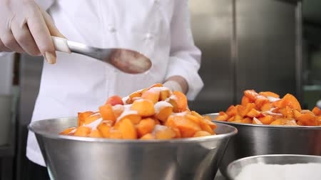 przetwory : hands pastry chef spread the sugar on the apricots fruit, prepare the jam in the industrial kitchen worktop.
