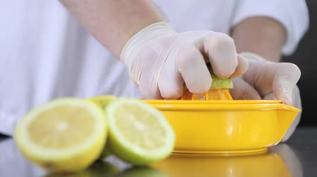 squeeze : hands pastry chef squeezed lemons on industrial kitchen steel worktop.