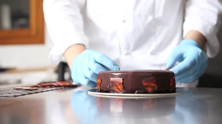 hands pastry chef prepares a cake, cover pouring chocolate icing and decorated with flakes, working on a stainless steel.