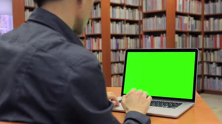 домашнее задание : Young Handsome Man Sits and Works on Green Screen Laptop in the Library.