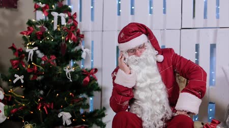 santa : Santa Claus Is Sit  Talking His Phone, Room with Fireplace  Christmas Tree, Gifts Stock Footage