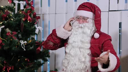 Санта шляпе : Santa Claus Talking His Smatrphone in Room with Christmas Tree and Gifts Стоковые видеозаписи