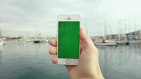 telefones : Man Hand Using Green Screen Mobile Phone Against in Front of the Pier with Yachts in the Sunny Day