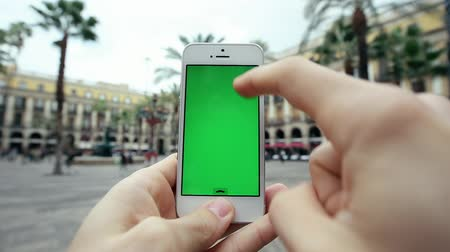 aplikacje : Man Using Mobile Cell with Green Screen Phone App Against Palm Trees and Waterworks Wideo