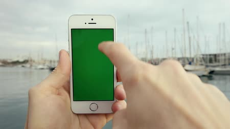 drží se za ruce : Man Hand Using Green Screen Smart Phone Against in Front of the Pier with Yachts in the Sunny Weather Dostupné videozáznamy