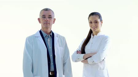 příznivý : Doctor Approaches Nurse in White Studio, They Look at the Camera and Smile Dostupné videozáznamy
