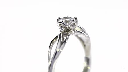 ring : Excellence White Gold Diamond Ring Turning on Themselves Against a White Background Stock Footage