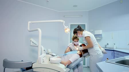 зубы : Dolly Shot of Dentist Examining Oral Cavity of a Patient with Toothache