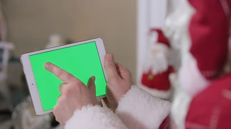 Санта шляпе : Santa Claus Work on Digital Tablet Green Screen. Tablet with Green Screen in Landscape Mode. Easy for tracking and keying. Стоковые видеозаписи