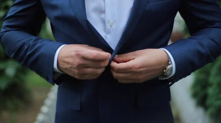 bogaty : Buttoning a Jacket. Stylish Man in a Suit Fastening Buttons on His Jacket Preparing to Go Out Close up.