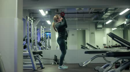head over : Young woman with beautiful sportive body fails to raise heavy dumbbell over head in gym profil mirror shoot Stock Footage