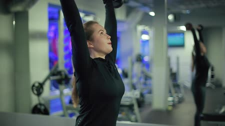 zayıf : Young woman with beautiful sportive body fails to raise heavy dumbbell over head in gym close up Stok Video