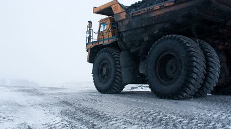Mining dump truck driving on snowy road from coal cut in Siberia in Russia. Machinery for heavy industry carrying fossil and minerals. Car with huge wheel. Energy and power. Work for dirty environment Stock mozgókép