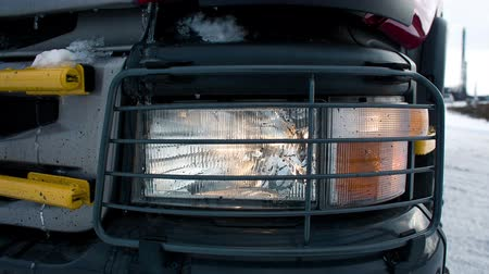 světlomety : Truck lights headlights. Machine on a snowy winter road on the way to the mine with coal in Siberia in Russia for transportation. Use headlamps of tipper closeup. Heavy industry. Energy and power
